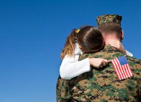 Child hugging military father
